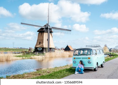 Alkmaar Netherlands April 2019, classic old vintage car van parked by historical windmill in Holland, Classic Minty Green and white VW Camper Van parked at countryside, woman posing with minivan