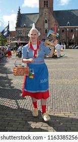 Alkmaar, The Netherlands - August 19, 2011: Cheese girl, kaasmeisje, in traditional costume is selling magazines at the Alkmaar cheese market