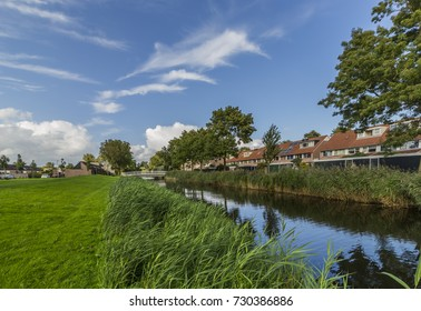 Alkmaar, the Netherlands. A beautiful view of the canal in the suburbs on a sunny day with a blue sky and white clouds on the background. One of the best touristic destinations in the Netherlands.