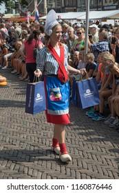 Alkmaar, Netherlands - July 20, 2018: Cheese girl, kaasmeisje, in traditional costume is selling cheese samples at the Alkmaar cheese market