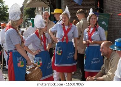 Alkmaar, Netherlands - July 20, 2018: Cheese girls, kaasmeisjes, in traditional costume waiting for the Alkmaar cheese market to start