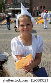 Alkmaar, Netherlands - July 20, 2018: Cheese girl, kaasmeisje, in traditional costume is showing a cheese sample at the Alkmaar cheese market