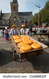 Alkmaar, Netherlands - July 20, 2018: Pair of men pushing a traditional wooden cart loaded with cheese wheels after beiing sold at the cheese market in Alkmaar