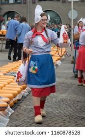 Alkmaar, Netherlands - June 01, 2018: Cheese girl, kaasmeisje, in traditional costume is selling cheese samples at the Alkmaar cheese market