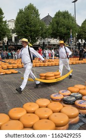 Alkmaar, Netherlands - June 01, 2018: Traditional cheese carriers carry cheeses on a wooden stretcher  in front of the Waag building during the cheese market