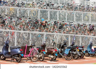 Alkmaar, Netherlands - June 11, 2019: Multi level outdoor bicycle and scooter parking near a trainstation in Alkmaar, Netherlands.