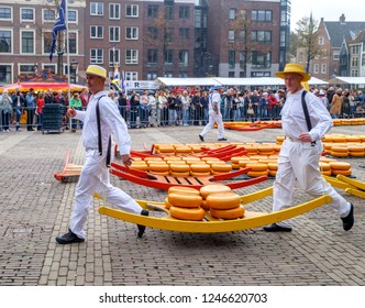 Alkmaar, Netherlands, September 2017. Two cheese bearers in traditional costume, running along with a berry full of round Dutch cheeses