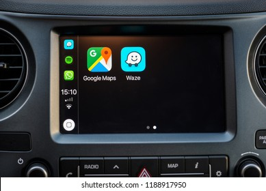 Alkmaar, The Netherlands - September 26, 2018: Apple CarPlay screen in modern car dashboard displaying Google Maps and Waze navigational apps. Those apps are compatible as per September 2018.