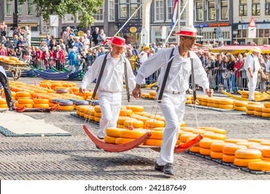 ALKMAAR, THE NETHERLANDS - SEPTEMBER 7: Carriers walking with many cheeses in the famous Dutch cheese market, September 7, 2012 in Alkmaar, The Netherlands. The event happens in the Waagplein square.