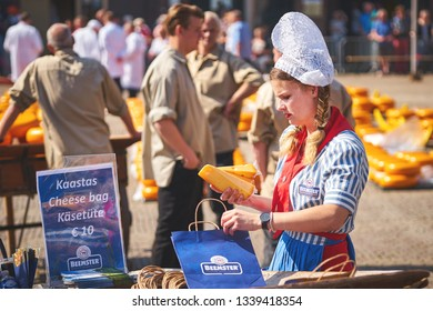 ALKMAAR/NETHERLANDS - April 20, 2018: Cheese girl packing cheese during the traditional cheese market in Alkmaar