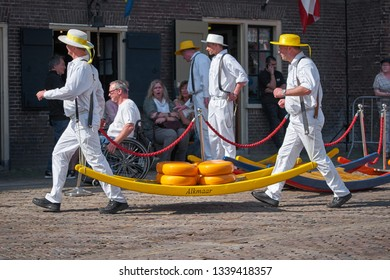 ALKMAAR/NETHERLANDS - April 20, 2018: Cheese carriers in a traditional uniform carry cheeses on a wooden stretcher during friday cheese market in Akmaar