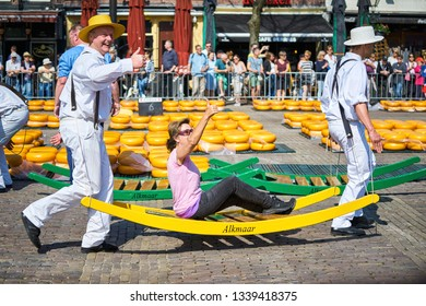 ALKMAAR/NETHERLANDS - April 20, 2018: Cheese carriers in a traditional uniform carry female tourist on a wooden stretcher during friday cheese market in Akmaar