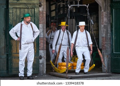 ALKMAAR/NETHERLANDS - April 20, 2018: Cheese carriers weighing the cheese on a big rural weigher at the traditional cheese market in Alkmaar