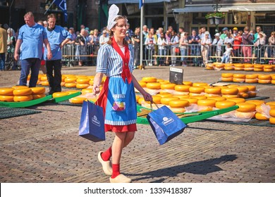 ALKMAAR/NETHERLANDS - April 20, 2018: Cheese girl in a traditional costume selling cheese during the cheese market in Alkmaar