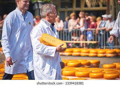 ALKMAAR/NETHERLANDS - April 20, 2018: Inspector testing and approving the quality of the cheese during traditional cheese market in Alkmaar