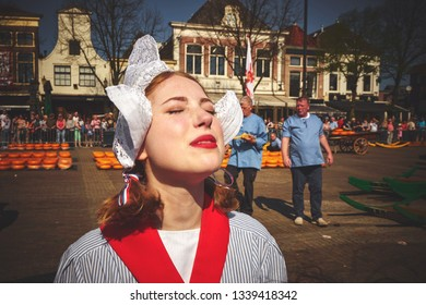 ALKMAAR/NETHERLANDS - April 20, 2018: Portrait of a cheese girl wearing dutch costume during the traditional cheese market in Alkmaar
