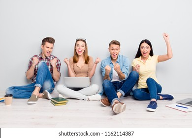 All aboute together brainstorming! Full length, legs, body, size portrait of youth sit on the floor isolated on light gray background and make hand like fists