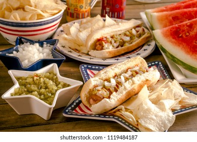 All American holiday celebration picnic table with hot dogs, chips and watermelon on red, white and blue themed plates and dishes
