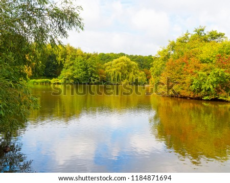 All around the nearly flat water of a small lake trees and shrubs begin to wear autumn colours. Weak late summer sky is reflected in the water.