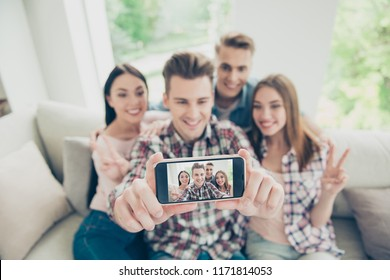 All attention to the smartphone! Focus on screen of modern phone with a blurry background with four young people take selfie sitting on a sofa in denim clothes