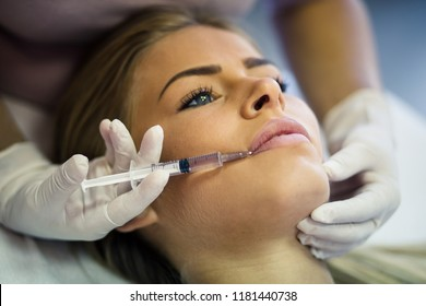 All for beauty. Doctor hands and patient having cosmetic Botulinum toxin lip filler injection. Close up. Copy space.