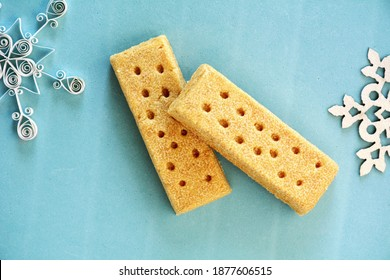 All butter shortbread fingers on aqua background in horizontal format in flat lay format.