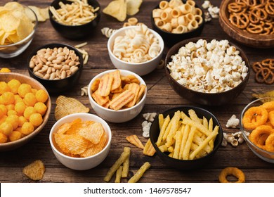 All classic potato snacks with peanuts, popcorn and onion rings and salted pretzels in bowl plates on wood. Twirls with sticks and potato chips and crisps with nachos and cheese balls. Top view - Shutterstock ID 1469578547