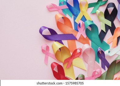 All color ribbons on pink background, cancer awareness, World cancer day