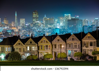 all colors of city lights turn up after the Victorian style houses with a modern city background.