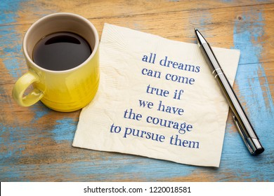 All dreams can come true if you have courage to pursue them - handwriting on a napkin with a cup of espresso coffee