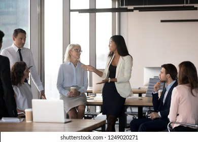 All employees attentive listening young asian female colleague gathered together in business meeting briefing at coworking area. Diverse international company staff negotiating having busy workday