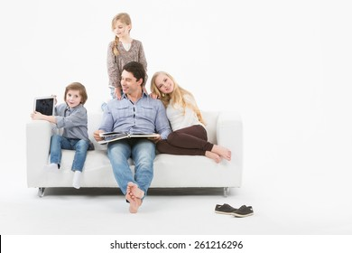 All family sitting on a white sofa on a white background and reading a book.