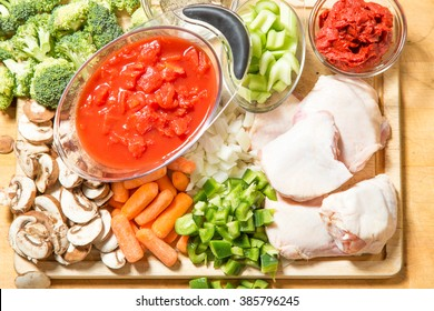 All the fresh raw ingredients for chicken cacciatore on chopping block ready to be assembled into a delicious dinner