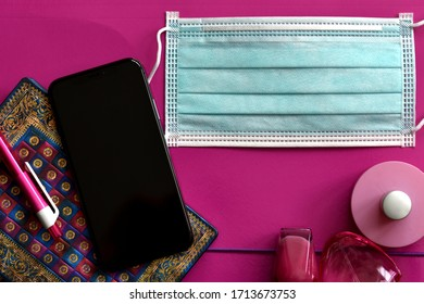 All the girl needs, new normalcy necessities, face mask, phone and knick-knacks on pink background. Copy space.
