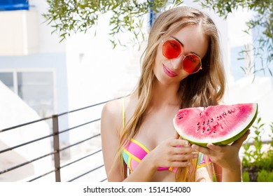 All Inclusive Cheap Summer Holidays. Young Happy Woman with Watermelon and pink sunglasses at beach Background. Summertime fun weekend. Beautiful girl in summer outfit. Selective focus. Hot Vacation