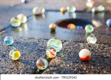All kinds of colored glass marbles in the light of the setting sun on the pavement with a marble pot in the tile.