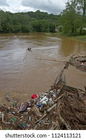 All kinds of human made debris, like plastic bottles, and branches, wood, and mud clog and pollute a river after a flood
