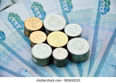 all kinds of russian coins in stacks on the one-thousand rubles banknotes. russian money for backgrounds and illustrations