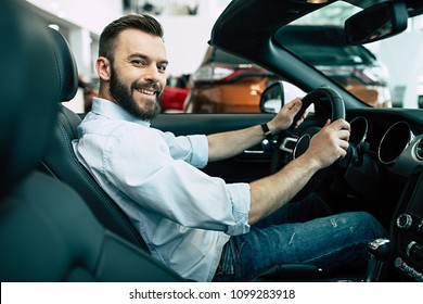 All my life I dreamed about cabriolet. An attractive smiling man buys a car, a guy evaluates the car's interior and looks into the camera while sitting at the wheel.