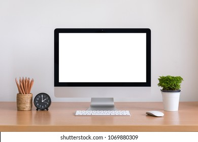 All in one computer, mouse, keyboard, clock, pencils and tree vase  on wooden table