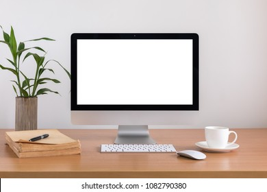 All in one computer, mouse, keyboard, old book, pen, coffee cup and plant vase  on wooden table