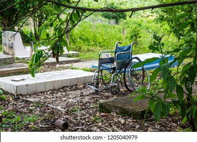 All pains are ending here: An empty, abandoned wheelchair, rotting on a tombstone.
