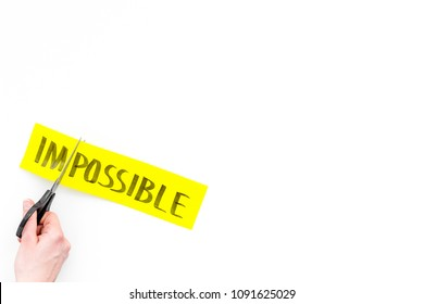 All is possible concept. Cutting the part im of written word impossible by sciccors. White background top view copy space