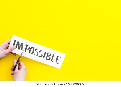 All is possible concept. Hands cutting the part im of written word impossible by sciccors. Yellow background top view copy space