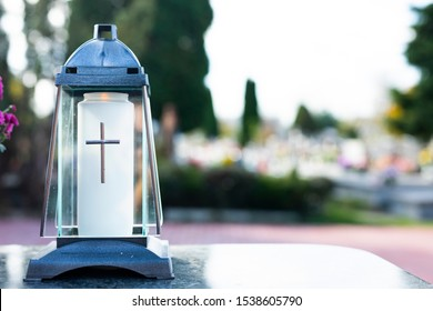 All Saints' Day. Lighted, elegant votive candle on a marble tombstone, on a cemetery. Visiting and decorating graves.