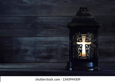 All Saints Day. Votive candle on dark background with copy space