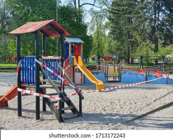 All slides in a public playground are sealed off with red and white plastic tape to prevent kids from playing during coronavirus lockdown. Covid-19 pandemic causes all public spaces to shut down.