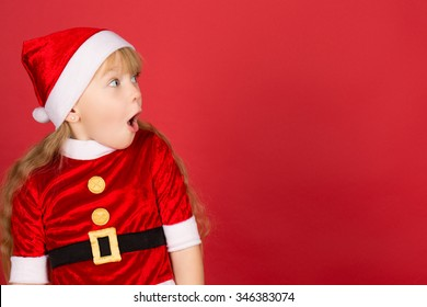 All these for me! Profile of a little cute girl wearing Christmas hat and Santa outfit looking away shocked with her mouth open copyspace on the side