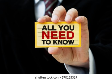 All you need to know. Businessman holding a card with a message text written on it