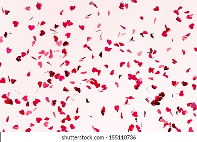 All You Need Is Love. Closeup view of confetti hearts of red color against pink background.